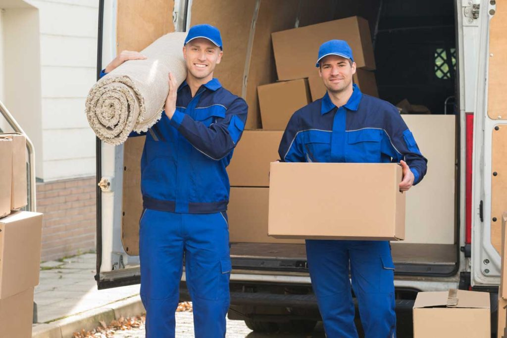 two men in blue uniforms holding a box and a carpet in front of open truck